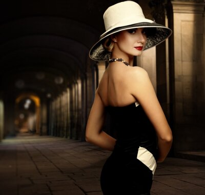 Canvas print Woman in black dress and big white hat alone outdoors at night
