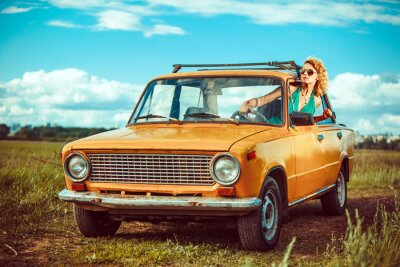 Canvas print Woman is driving an old yellow car. Rural background.
