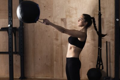 Canvas print Woman lift weight ball at the gym