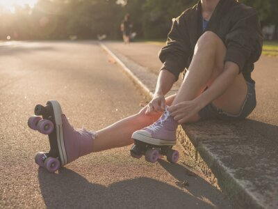 Canvas print Woman putting on roller skates in park