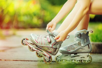 Canvas print Woman putting on rollerblades outdoors. Close up.