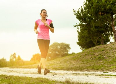 Canvas print Woman Running In Countryside at beautiful sunset.
