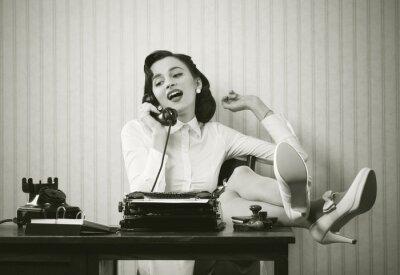 Canvas print Woman talking on phone at desk