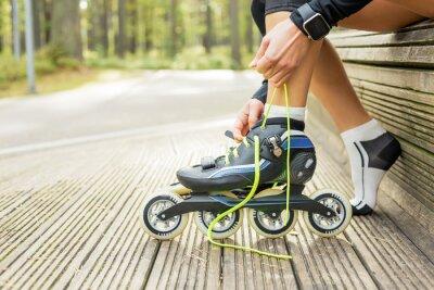 Canvas print Woman tying roller skates