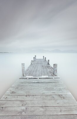 Canvas print Wooden pier on lake in a cloudy and foggy mood.