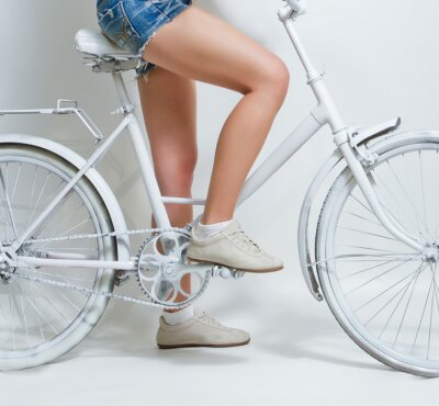 Canvas print Young girl riding a white vintage bicycle