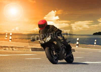 Canvas print young man riding big bike motorcycle against sharp curve of asphalt high ways road with rural lake scene use for male adventure activities and motor sport hobby on holiday vacation