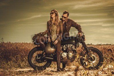Canvas print Young, stylish cafe racer couple on the vintage custom motorcycles in a field.
