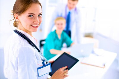 Canvas print Young woman  doctor holding a tablet pc
