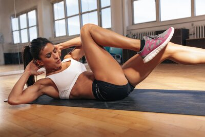 Canvas print Young woman doing a sit ups