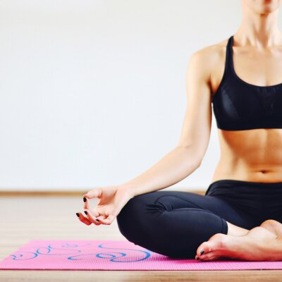 Canvas print Young woman doing yoga indoors - body part