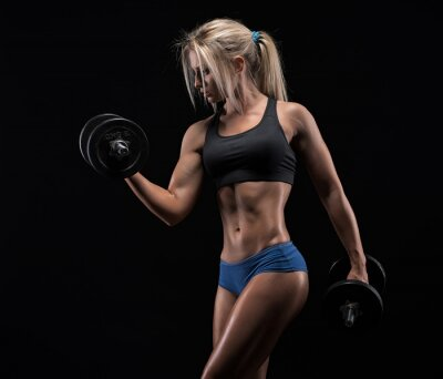 Canvas print Young woman lifting the dumbbells
