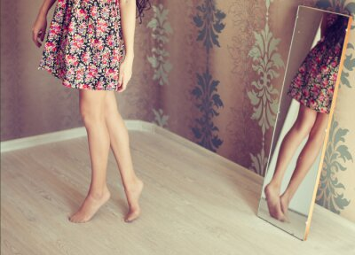 Canvas print young woman turns the mirror