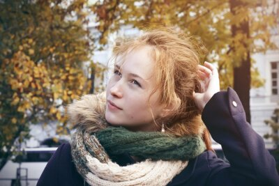 A beautiful red-haired girl in a blue coat, whose hair is braided in a tail, corrects them with her hand, standing in the middle of the city Park in the autumn.