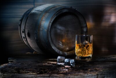 Wall mural A glass of whiskey with ice on background barrel