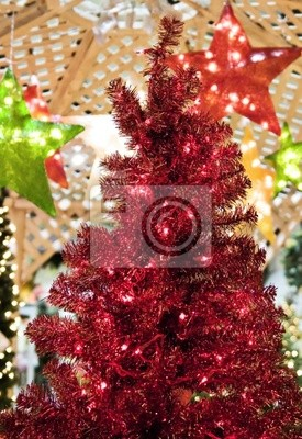 A red lighted christmas tree surrounded by stars.