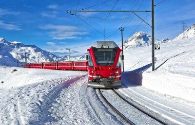 Wall mural A red swiss train running through the snow