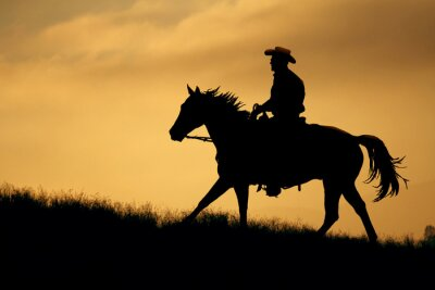 Wall mural A silhouette of a cowboy and horse walking up a meadow with an  orange and yellow background sky.