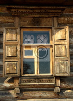A window with shutters in an old wooden house