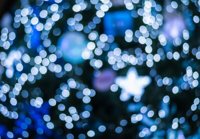 Wall mural Abstract blurred blue light bokeh at christmas tree in the night background