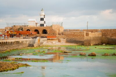 ACRE ISRAEL  MAY 04 2015: Sunset scene of a Templar Fortress remains lighthouse restaurants visitors and Haifa bay in the old city of Acre Israel