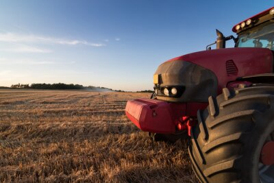 Wall mural Agriculture tractor on a stubble field