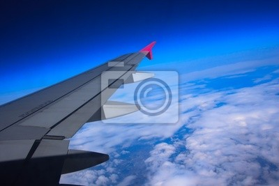 Aircraft wing flying high above the clouds