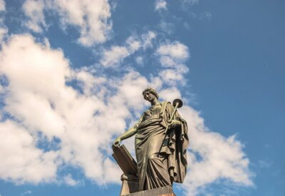 Ancient sculpture (18th century) of  ancient Greek muse of  history of Clio against  background of sky and clouds