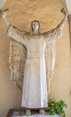 Ancient sculpture depicting praying catholic saint Catherine of Siena