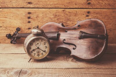Wall mural Antique clock and old violin over vintage wooden table