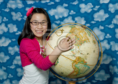 Wall mural Asian Girl points to a location on a globe
