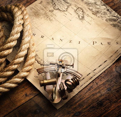 Astrolabe and rope on vintage map. Adventure stories background.