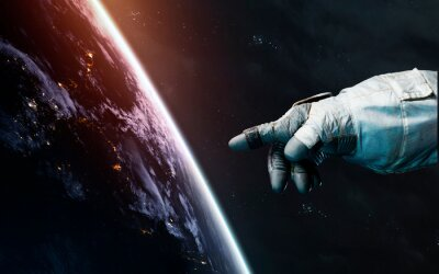 Astronaut hand points to Earth planet. Awesome science fiction render. Elements of this image furnished by NASA