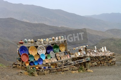 Wall mural ATLAS, MOROCCO - JULY 10: Souvenirs stand on the side of the road on July 10, 2013 in Atlas Mountains, Morocco. Road in Atlas Mountains very popular tourist route in central Morocco.