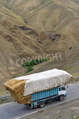 Wall mural ATLAS, MOROCCO - JULY 13: Overloaded truck staying on road, July 13, 2013 in Atlas Mountains, Morocco. Road in Atlas Mountains very popular tourist route in central Morocco.