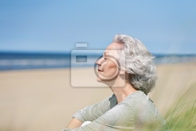 attractive, gray-haired woman enjoying the sea
