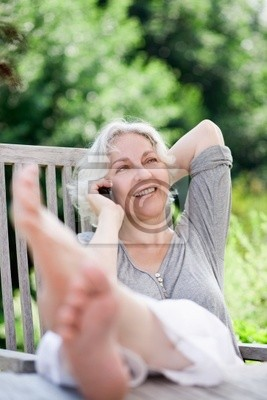 attractive, gray-haired woman on the phone in a summer garden