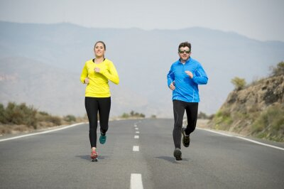 Wall mural attractive sport couple man and woman running together on asphalt road mountain landscape