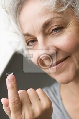 Attraktive Seniorin hält lächelnd eine Kontaktlinse
