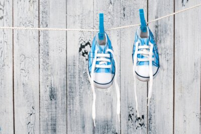Wall mural Baby shoes hanging on the clothesline.