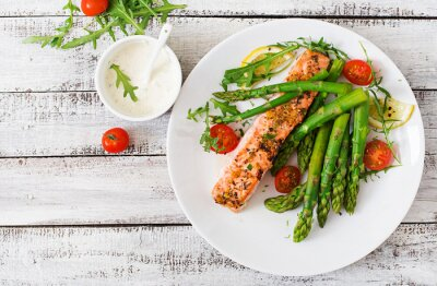 Wall mural Baked salmon garnished with asparagus and tomatoes with herbs. Top view