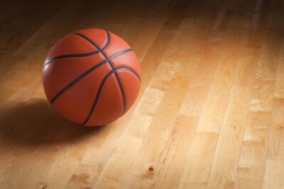 Wall mural Basketball on hardwood court floor with spot lighting
