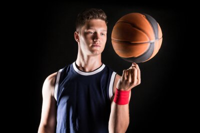 Wall mural Basketball player spinning ball on finger