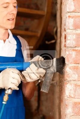 Bauarbeiter entfernt Putz aus Fuge