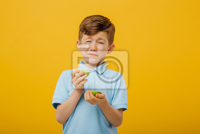 Wall mural beautiful boy taste a fresh lime taste sour grimace, facial emotions negative, in blue T-shirt, isolated yellow background, copy space