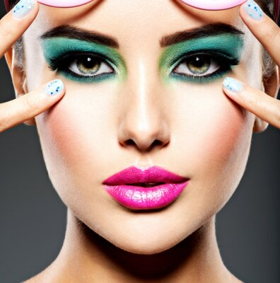 Wall mural Beautiful Face of a woman with green vivid make-up of eyes
