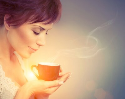 Wall mural Beautiful Girl Enjoying Coffee. Woman with Cup of Hot Beverage