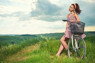 Wall mural beautiful girl with vintage bike outdoor, Tuscany summer time