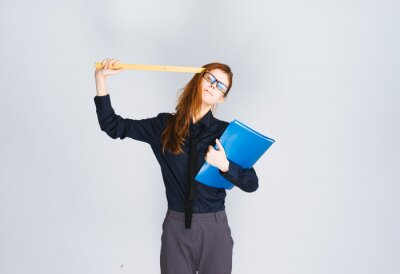 beautiful red-haired girl with a blue folder in her hands leaned a ruler to her head, a girl with glasses