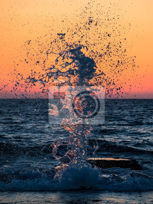 Wall mural Beautiful sea splash against the background of the fading sun